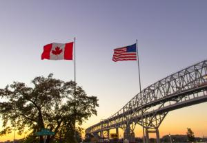 One type of immigration bond allows a detainee to leave the country voluntarily. Shown here is the Blue Water Bridge, which connects Port Huron, Michigan to Sarnia, Ontario. The flags for both countries are shown side by side.